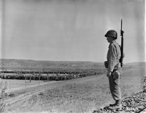 Der amerikanische Gefreite Paul Drop bewacht ein Lager, in dem Kriegsgefangene aus den Kämpfen im Ruhrgebiet untergebracht sind. Fotografie der US-Armee, 21. April 1945. Quelle: National Archives Washington, DC.