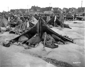 Viele der Rheinwiesenlager grenzten sehr nah an Ortschaften, wie hier in Ludwigshafen-Rheingönheim, wo die Zäune direkt an die Häuser reichten. Fotografie der US-Armee, 28. Mai 1945. Quelle: National Archives Washington, DC.